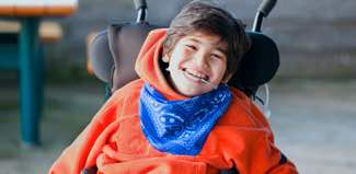 Photo: Smiling boy with bandana in wheelchair