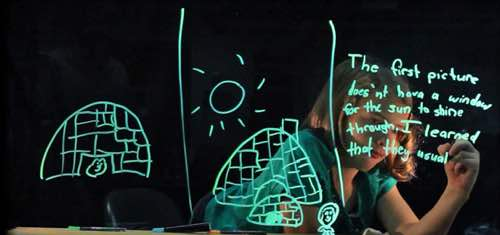 Photo: Child writing on screen with drawing of 2 igloos, only one has a window. and she's writing that The first picture doesn't have a window for the sun to shine through. I learned that . . .