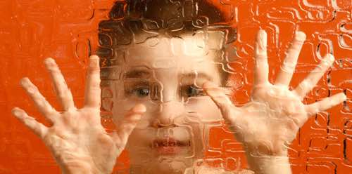 Photo: Child looking through textured glass with blurred image