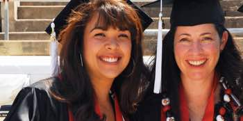 Photo: 2 smiling graduates dressed in academic regalia
