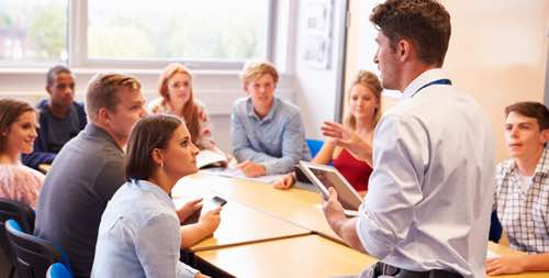 Photo: Group of students around table with standing instructor holding iPad