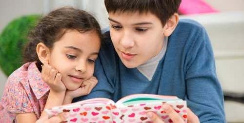 Photo: 2 young children reading a book
