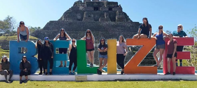 Photo: Liberal Studies students pose with giant letters spelling out BELIZE in front of a Mayan pyramid ruin.