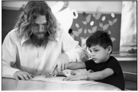 Unidentified student teacher gives a lesson in Braille, 1970s. Holding his hand over his student's hand to guide him, a man teaches Braille to a young boy.