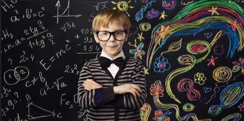 Boy in front of blackboard with equations and art