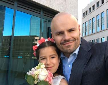 Photo: Oscar Grajeda poses in city setting with a little girl holding bouquet of flowers