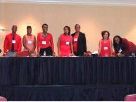 Photo: Student participants in conference pose behind conferencetable