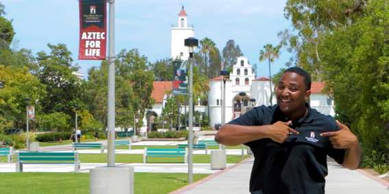 Photo: Man standing outdoors at SDSU with building in background, he's pointing to his SDSU logo shirt and standing near a sign that reads Aztec for Life.