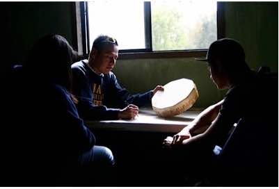 Photo: NAISC scholar mentoring youth with small drum at table near window.