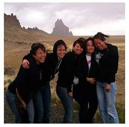 Photo: Group of NAISC women laughingly pose for photo in front of Ship Rock