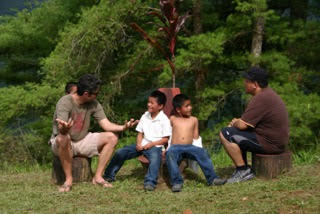 Photo: Students and little boys sit on tree stumps and chat