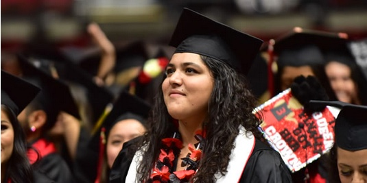 Photo: Young senior student in graduation regalia in crowd of other graduates, and she's looking upwards with a smile.