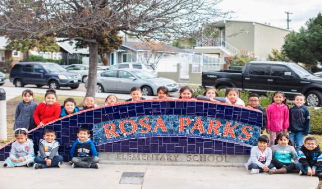 Photo: Children pose in front of Rosa Parks elementary school sign