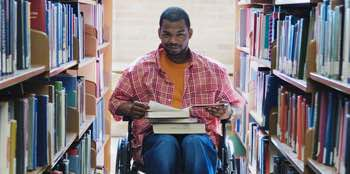 Photo: Student in wheelchair looking at books in library