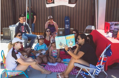 SDSU students sit on beach chairs outside and read books to young children.