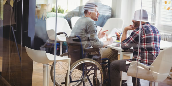 man in wheelchair at conference table with trainer
