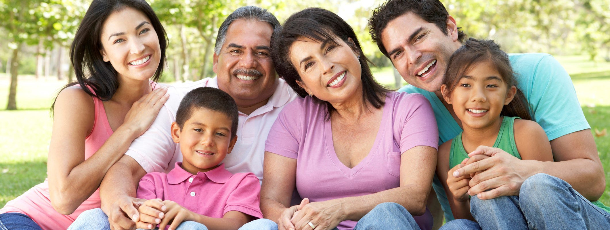 Latino family sitting together at a park