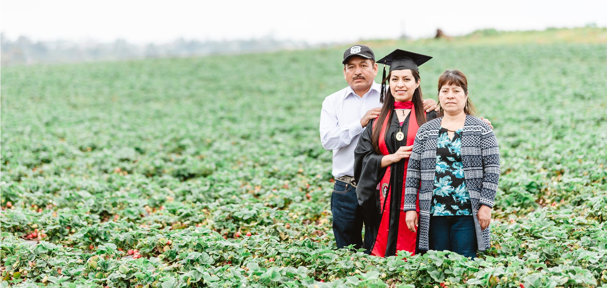 Erica Alfaro and her parents standing in a strawberry field