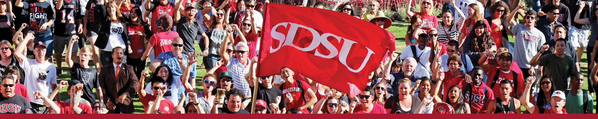 faculty, staff and students march with SDSU flag