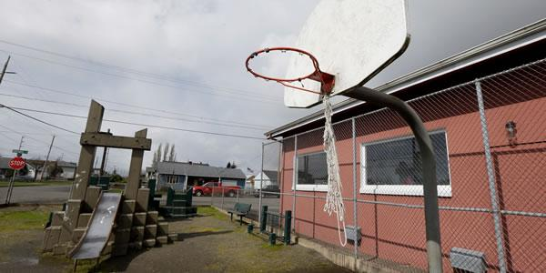 Basketball hoop and a red building is to the side of the hoop.