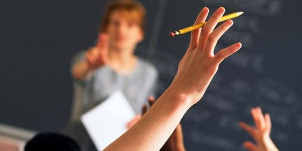 Student raising their hand in a school classroom.