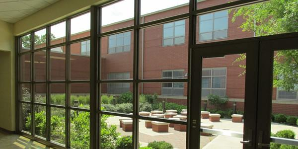 Windows display a courtyard with seating and plants with a brick building behind the courtyard.