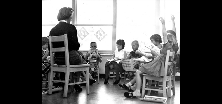 Photo of Mrs. Betty Holt sits with several students.