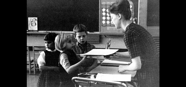 Photo of a school teacher talking to students.