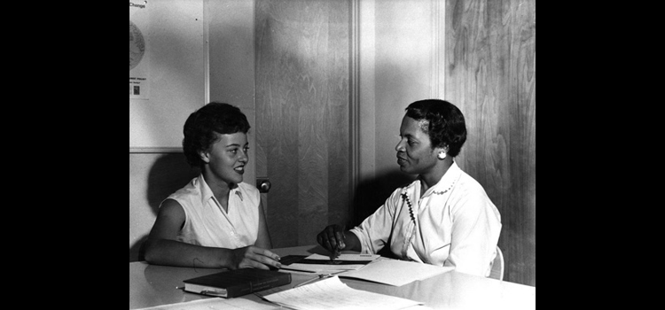 Photo two women sit at a conference table during an education interview. .
