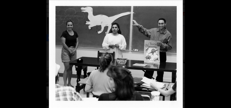 Photo students use a dinosaur book and cutout to illustrate their presentation.