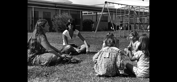Photo of children and students on a playground.