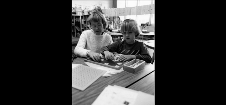 Photo of a student and a teacher playing a number game.