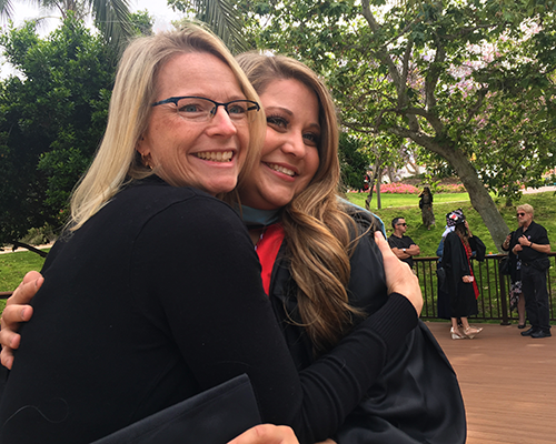 Faculty member, Rebecca Koo, embraces Sarah Zillweger on her graduation day