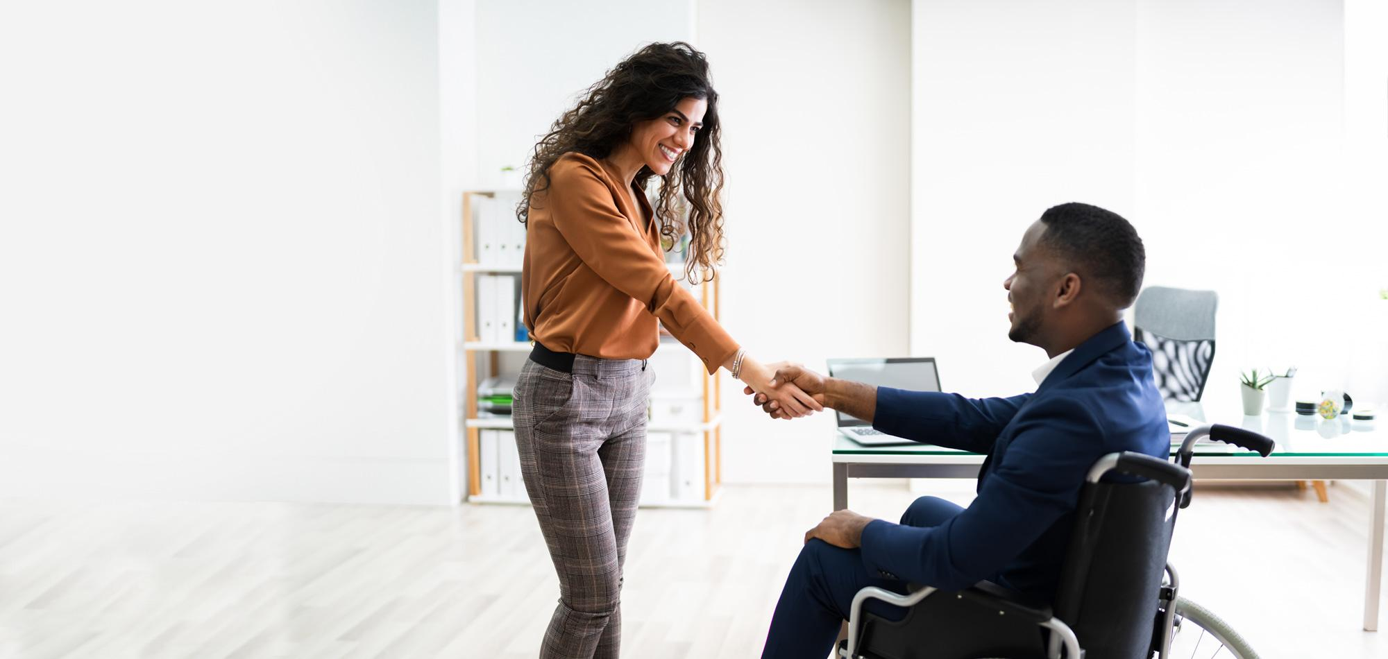 woman shaking hand of man in wheelchair
